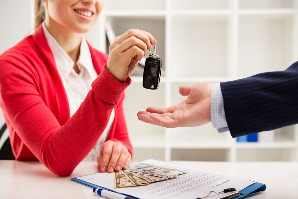 Woman handing car keys to man