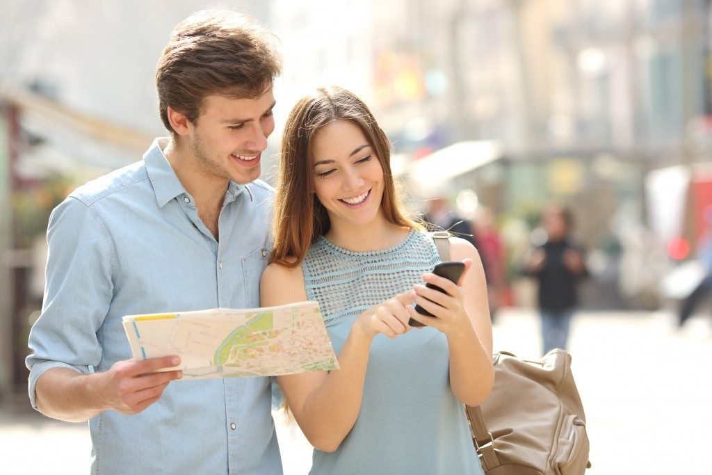 Couple of tourists consulting a city guide and smartphone