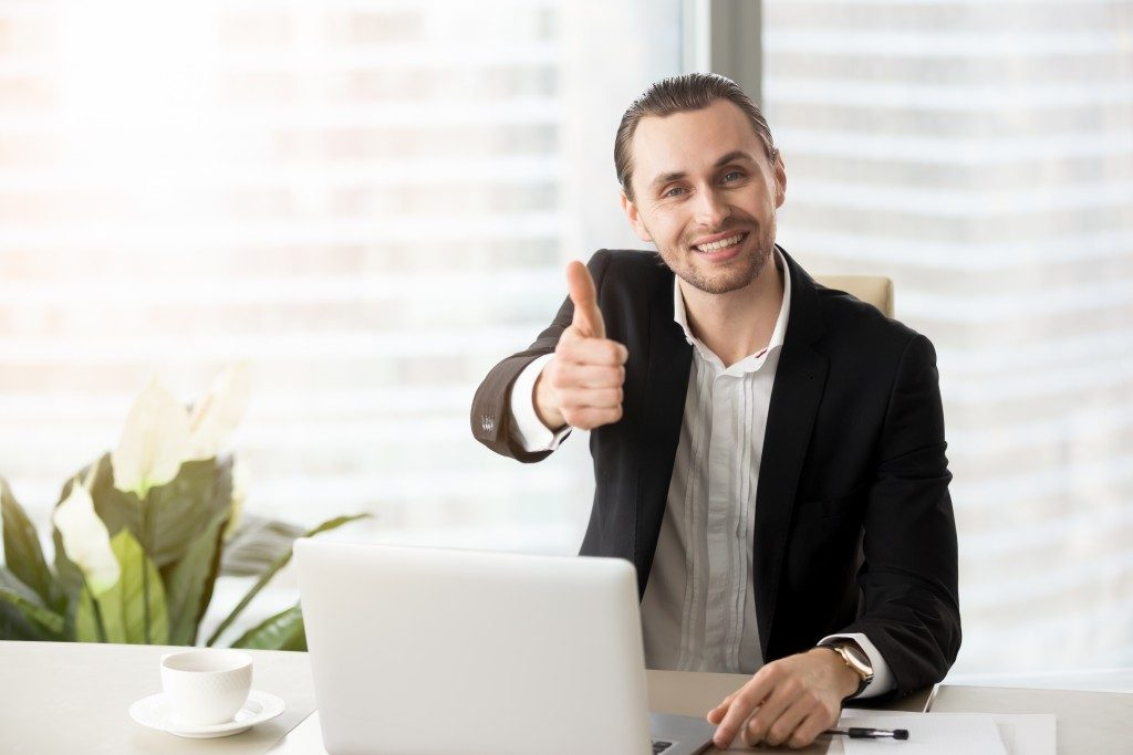 businessman doing thumbs up while working