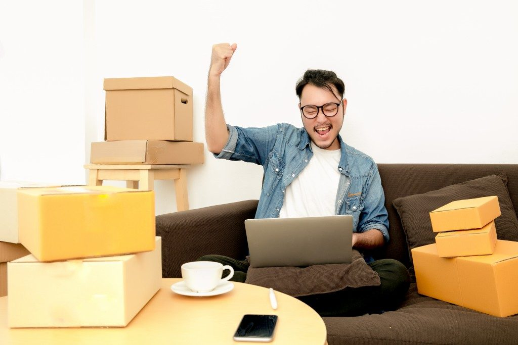 Man selling online with boxes around him