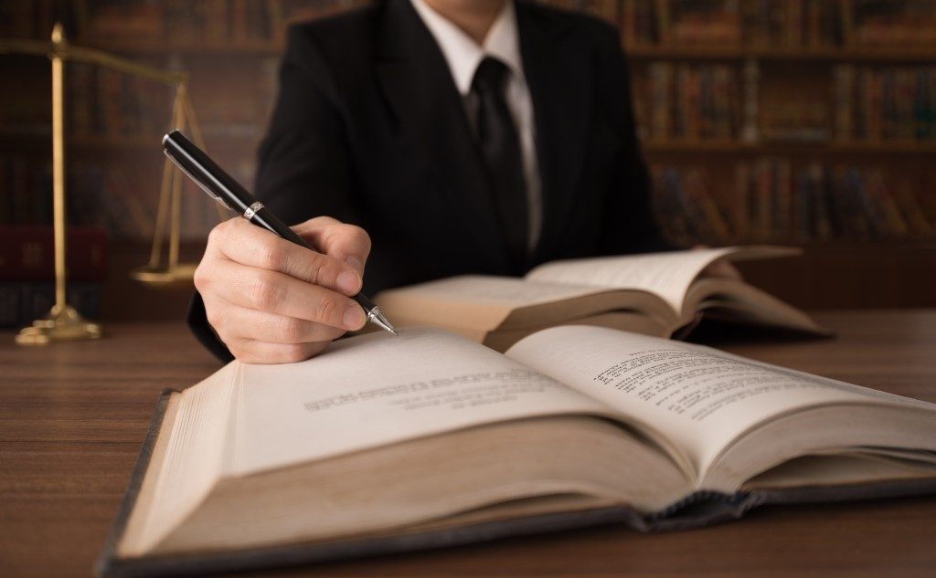 lawyer writing with a book