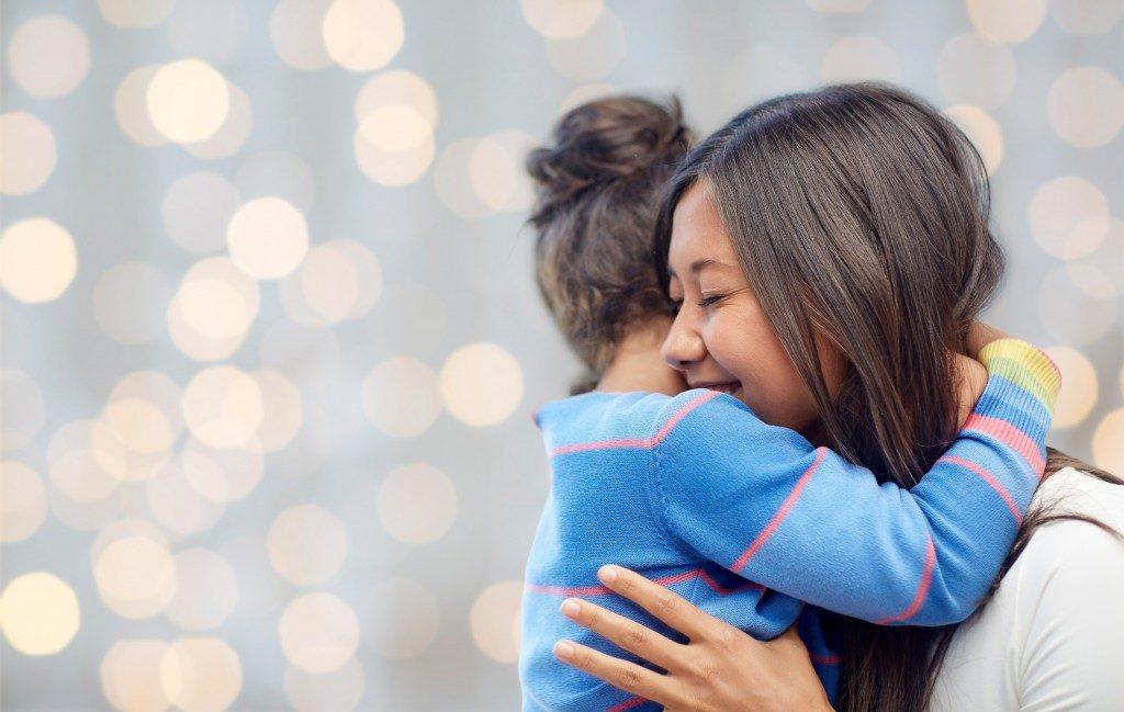 woman hugging a little girl