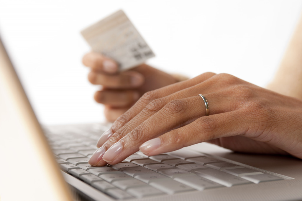 woman using laptop holding card