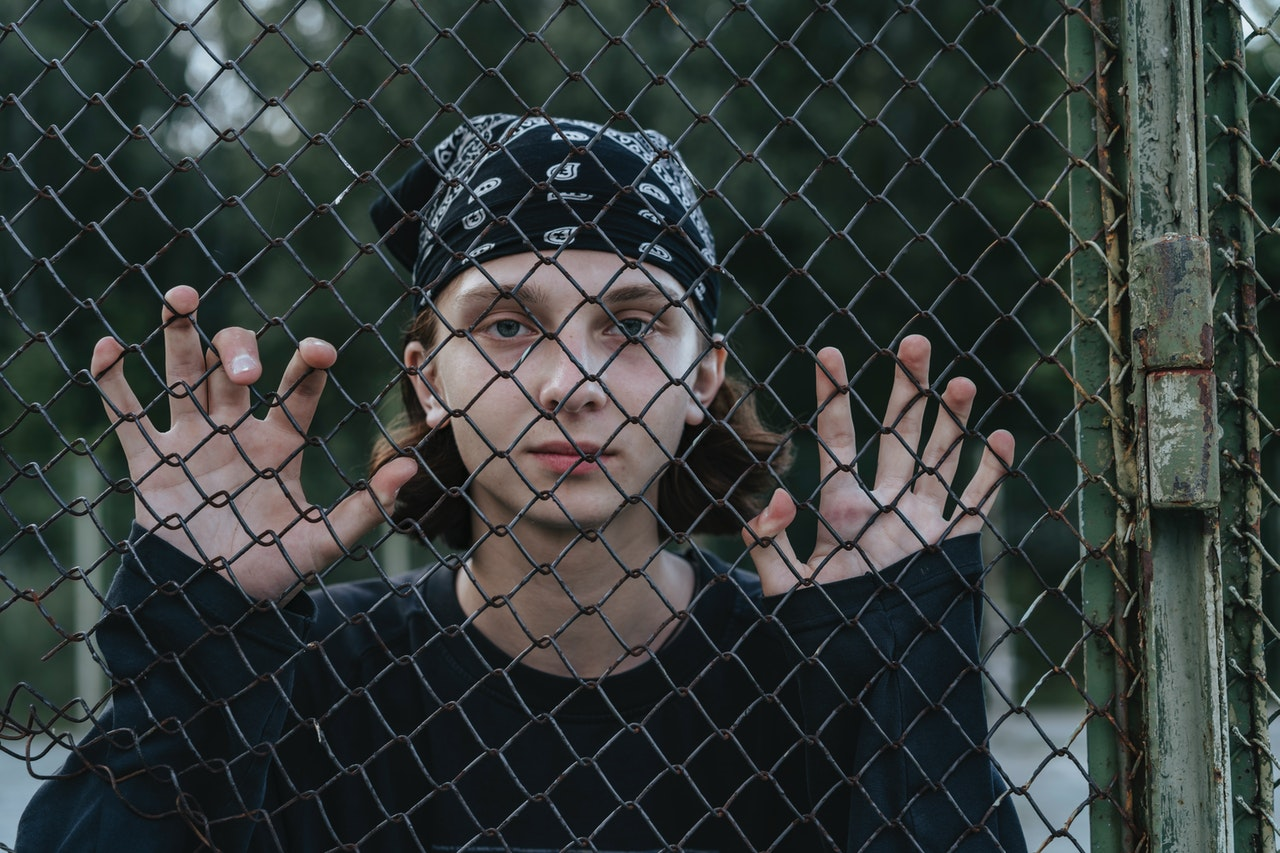 person looking outside a fence