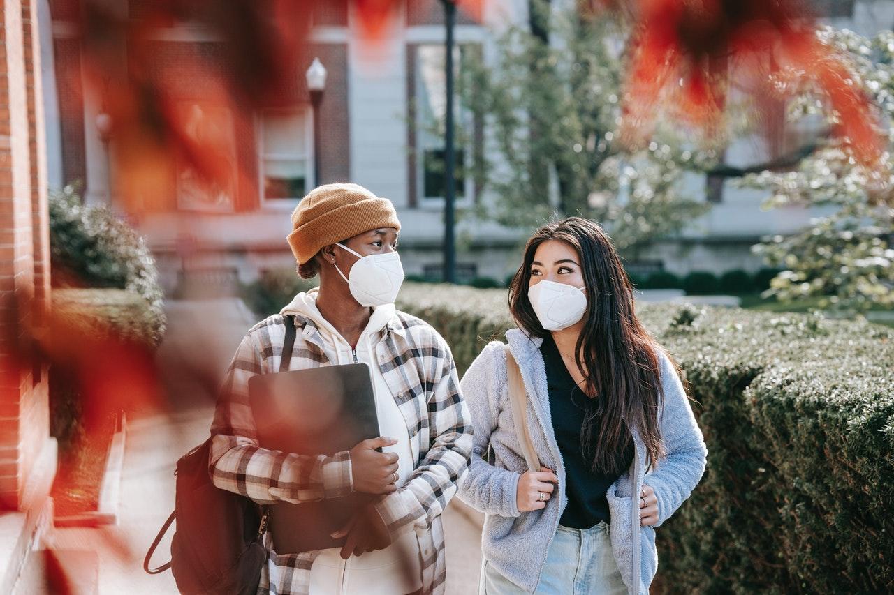 women walking together wearing masks